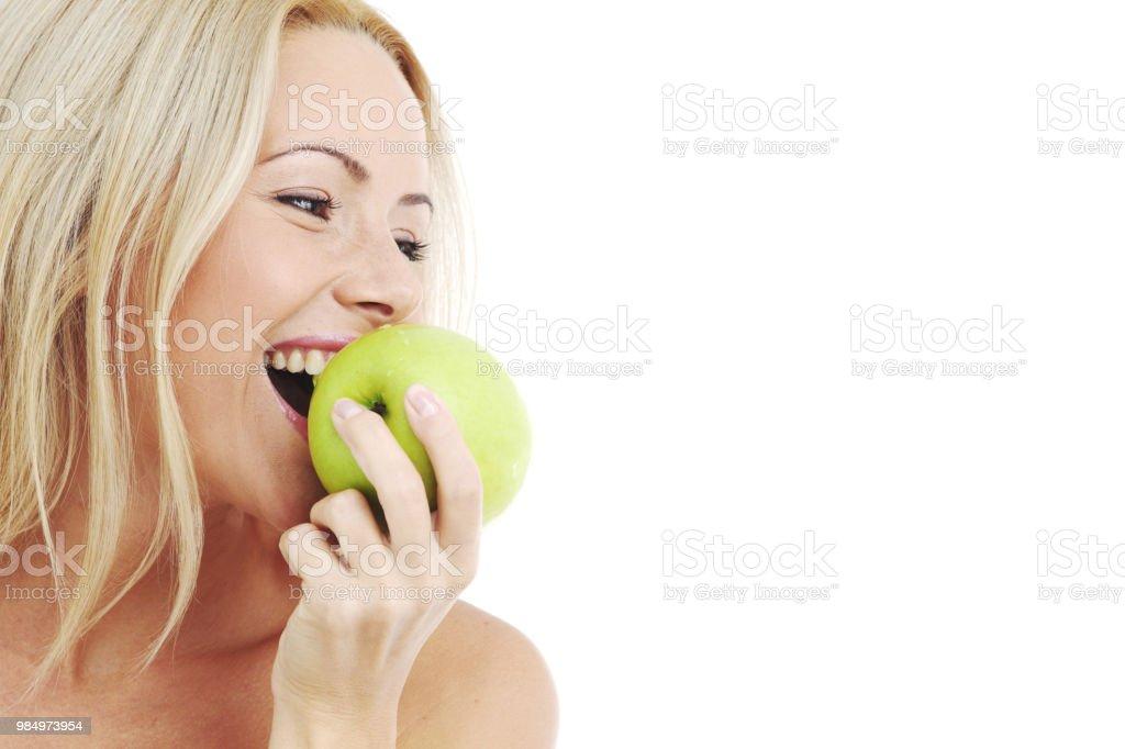 blond woman eat green apple on white stock photo