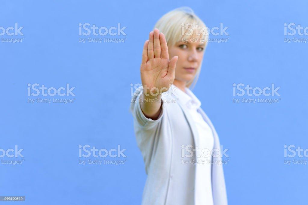 Blond kvinna ger ett stopp tecken - Royaltyfri Allvarlig Bildbanksbilder