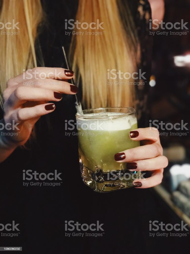 Blond woman holding a cocktail glass at night stock photo