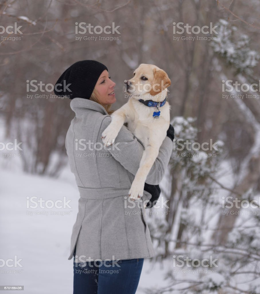Blond woman holds yellow lab puppy over her shoulder gazing adoringly at him stock photo