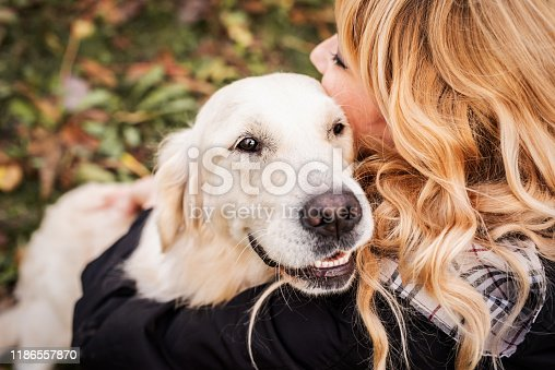 Pet care concept. Happy blond woman hugging her retriever dog in the park