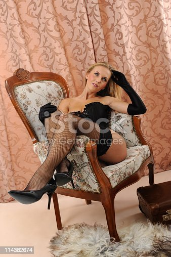 istock Blond Woman in Black Corsage relaxing Baroque Chair 114382674