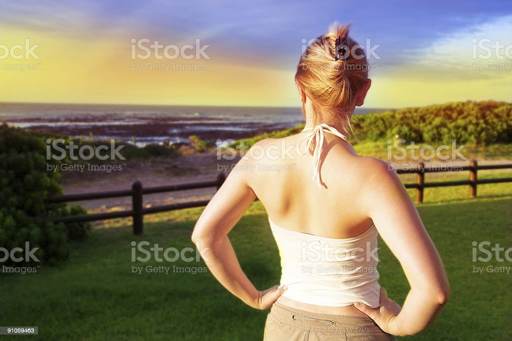 blond woman in sunset light at sea shore royalty-free stock photo