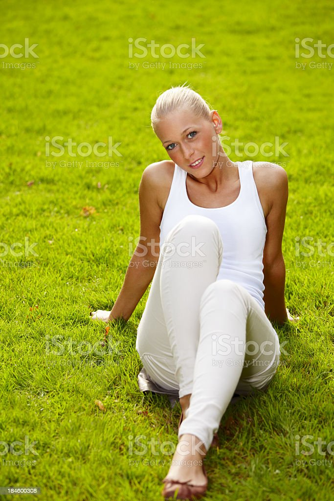 Blond woman in white clothes sitting in grass stock photo