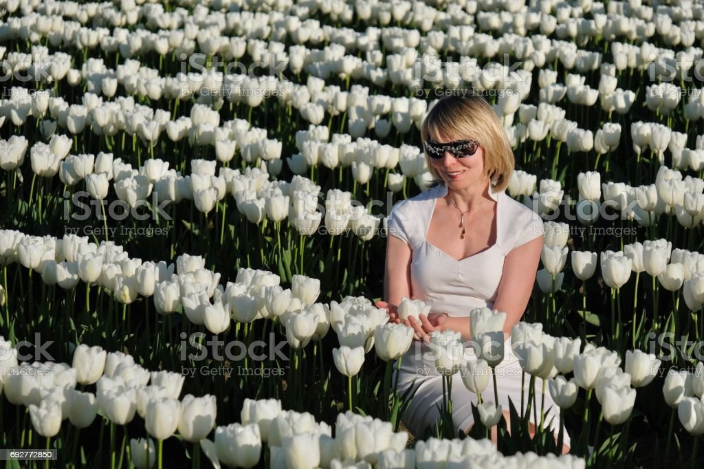Blond woman in white flowers. stock photo