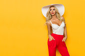 Beautiful blond woman in white sun hat, corset and red trousers is posing with hands in pockets and looking away. Three quarter length studio shot on yellow background.