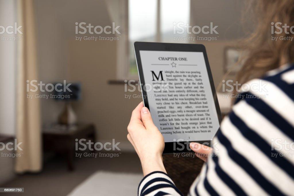 Blonde vrouw is digitale tablet in handen te houden en is het lezen van digitale e-book thuis foto