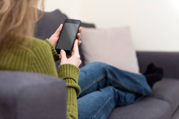 Blond woman is sitting at home looking at a mobile phone screen technology background stock photo