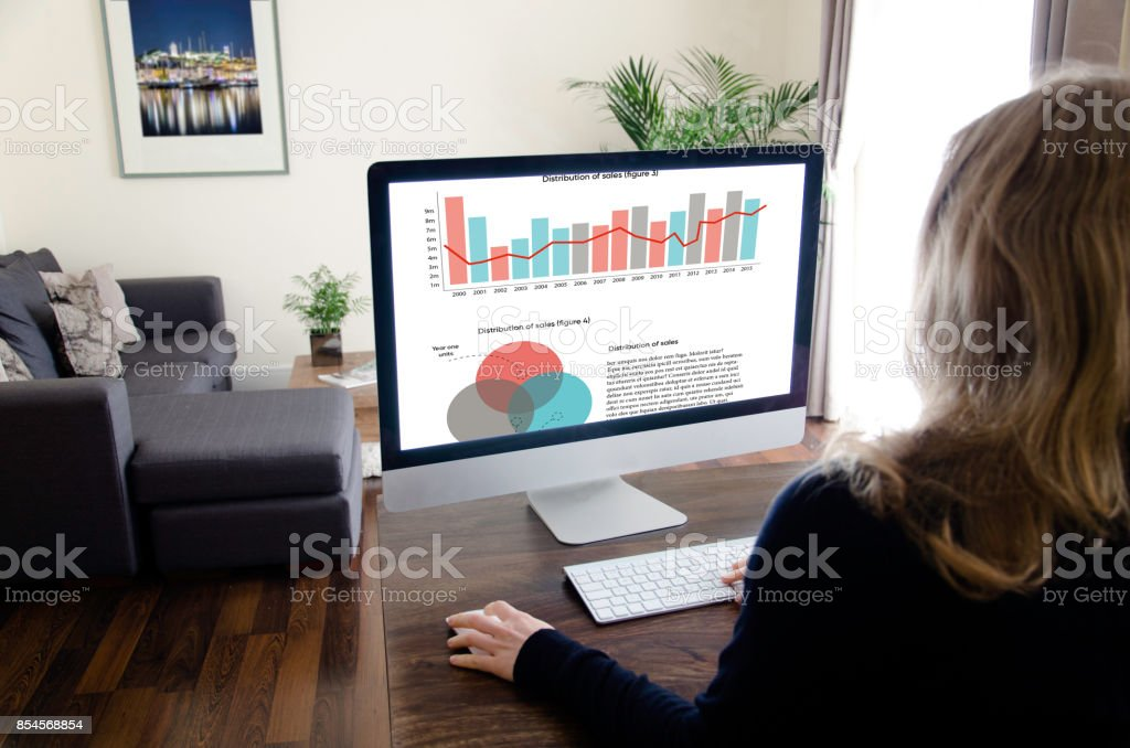 A blond woman is sitting in a living room on a desk and is working on a desktop computer. stock photo