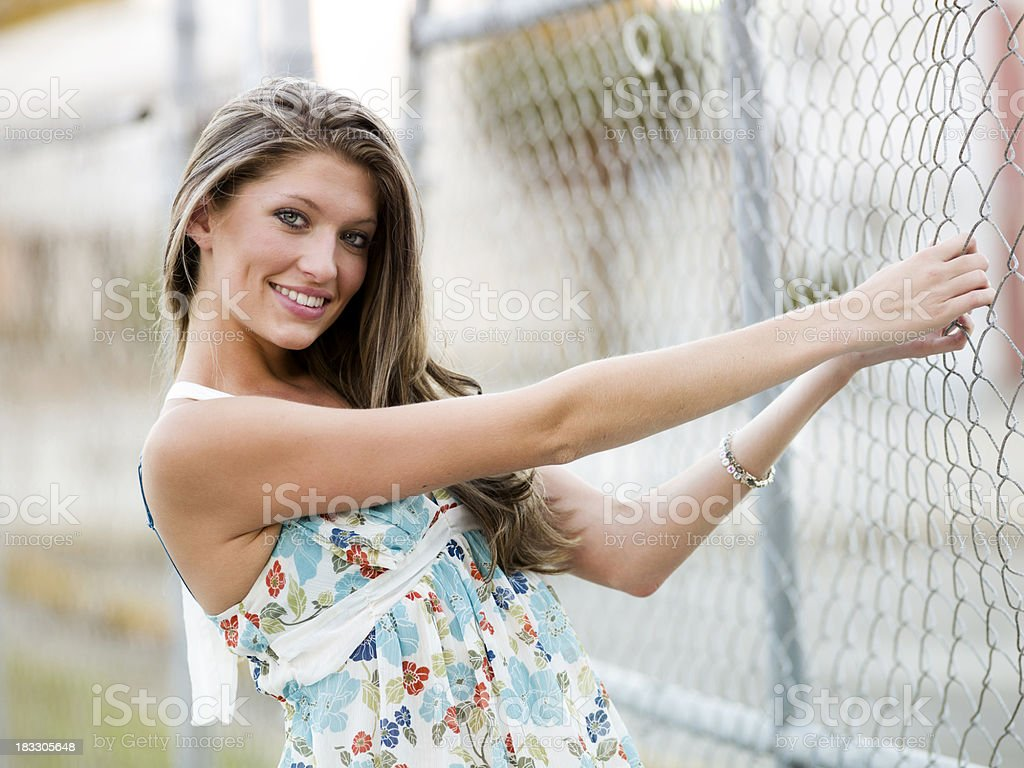 blond woman leaning on a fence royalty-free stock photo