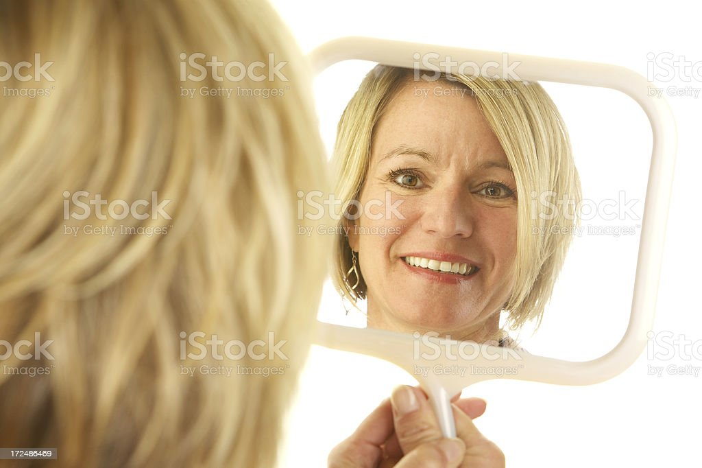 Blond Woman Looking at Her Reflection in a Mirror royalty-free stock photo