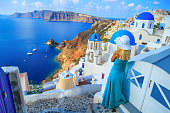 Discovering Greece.Beautiful blond woman enjoying vacations in Santorini, Greece. Looking at view.