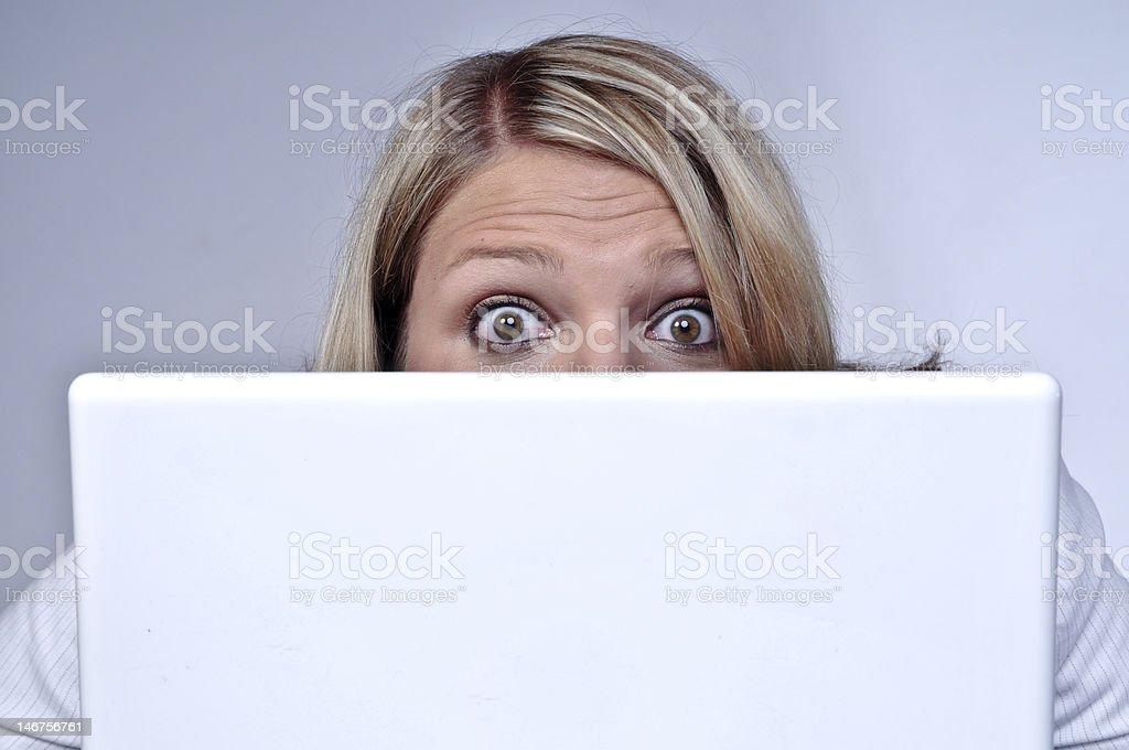 Blond Woman Looking Behind Laptop royalty-free stock photo