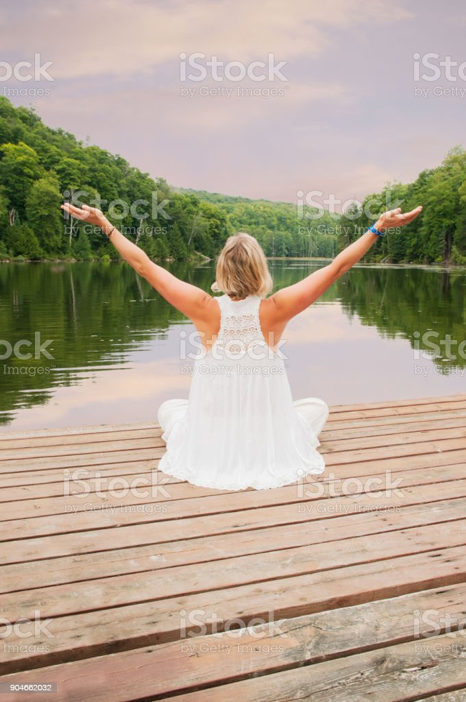 Blond woman meditating with arms open by a lake stock photo