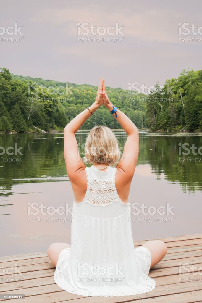 Blond woman meditating with hands above her head by a lake stock photo