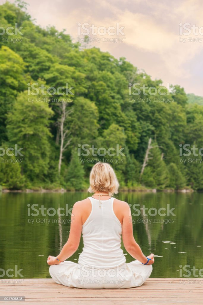 Blond woman meditating with hands on knees by a lake stock photo