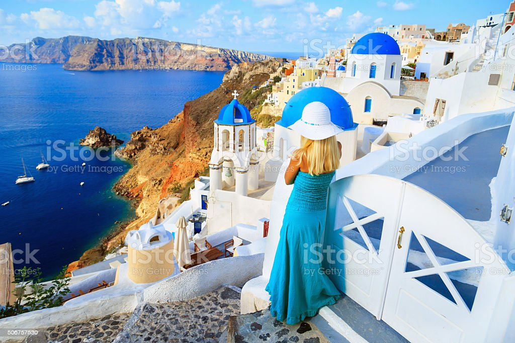 Blond woman on the streets of Santorini looking at sea stock photo