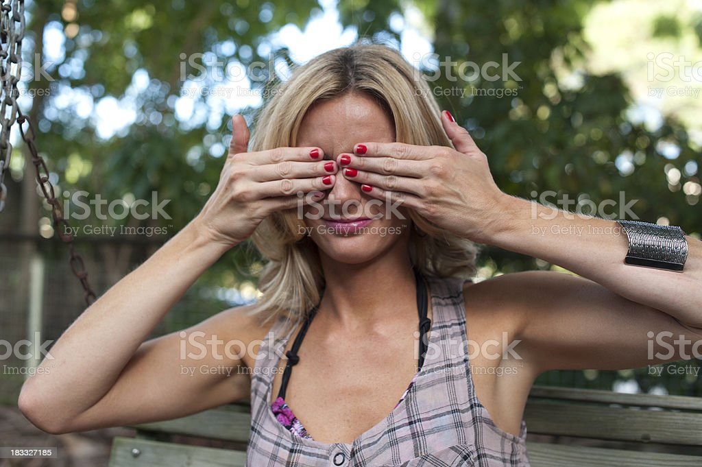 Blond woman outdoors holding her hands over her eyes. royalty-free stock photo
