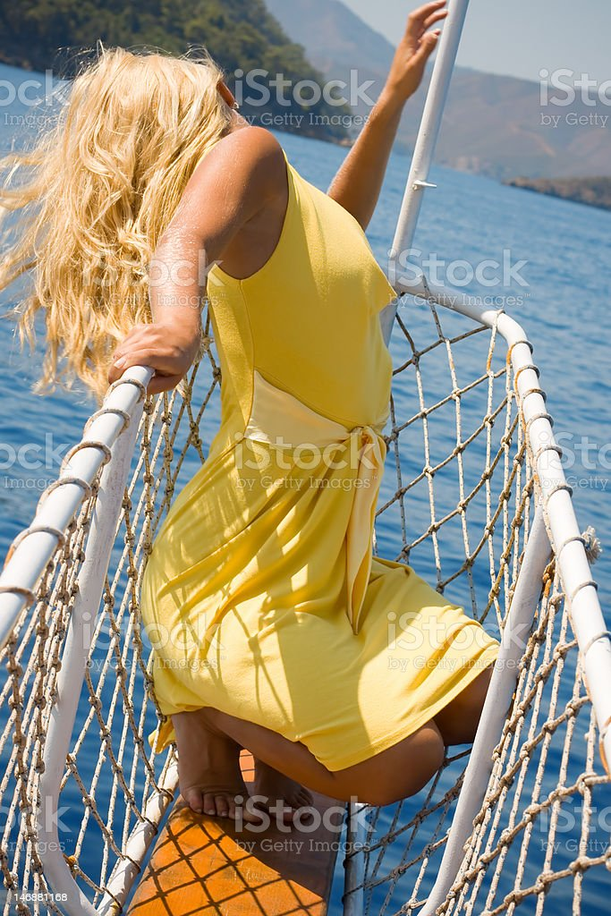 Blond woman posing on the ship's bow stock photo