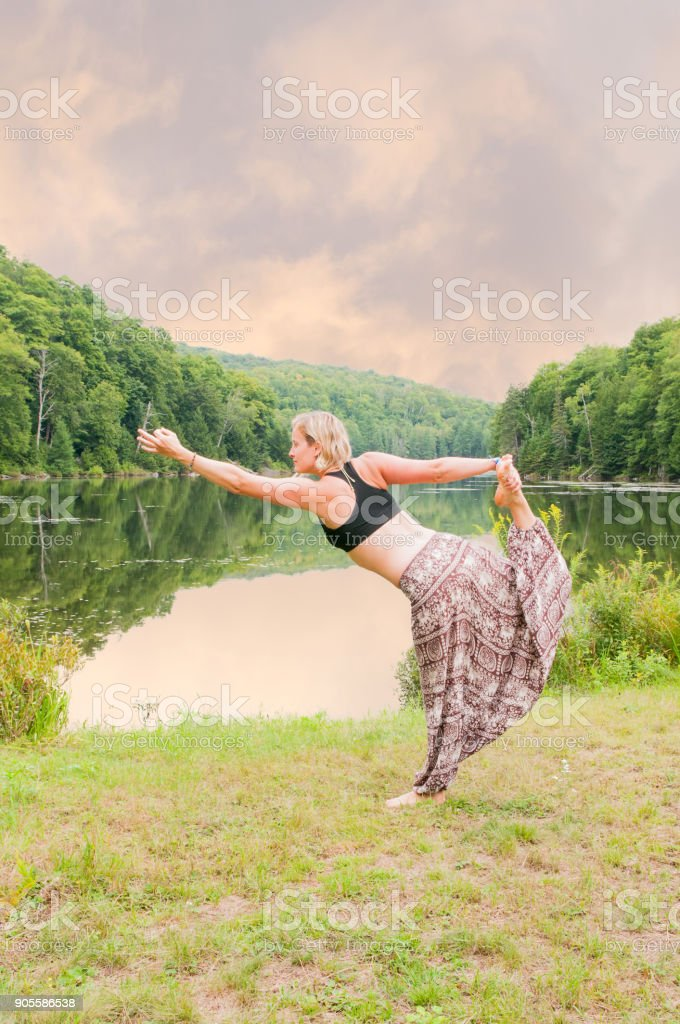 Blond woman practicing yoga by a lake stock photo