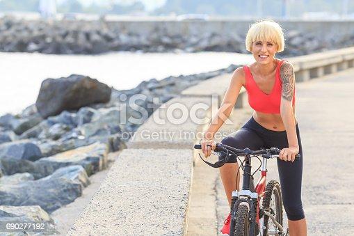 Smiling young woman cycling near the sea. Looking at camera.