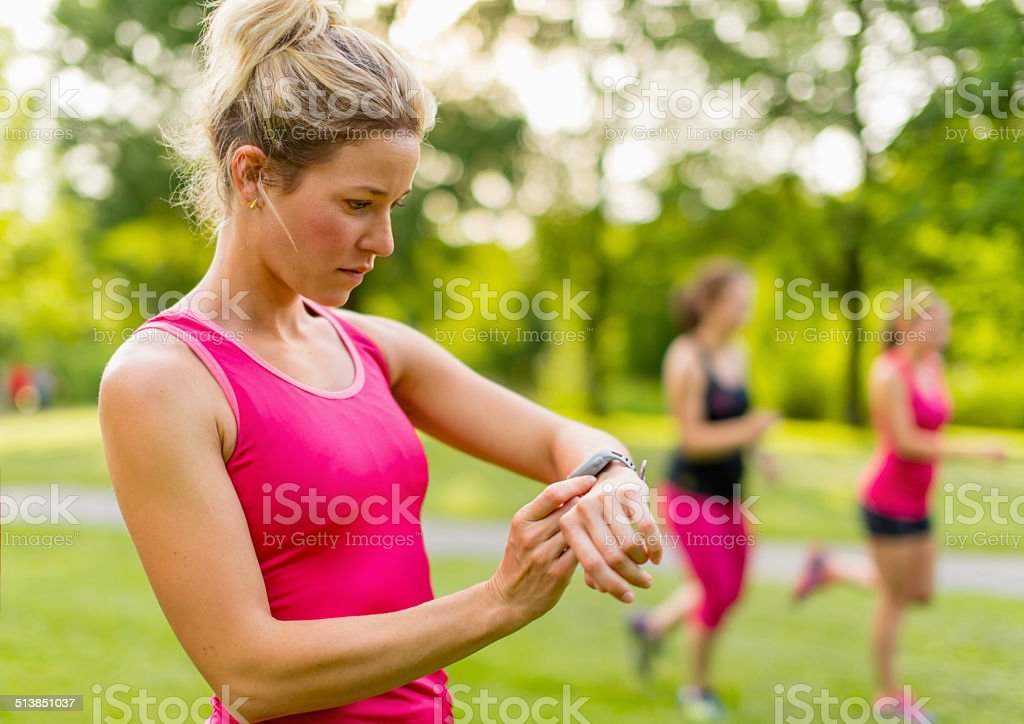 blond woman setting her timer before jogging stock photo