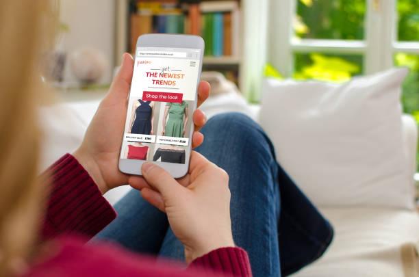 blonde frau, die zu hause auf dem sofa sitzen und ist auf der suche auf einer website für digital über das internet zum online-shop - sofa online kaufen stock-fotos und bilder