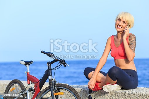 Blond woman sitting legs crossed on sea quay and using smart phone. A bike next to her.