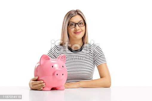 Blond woman sitting with a piggy bank and smiling at the camera isolated on white background