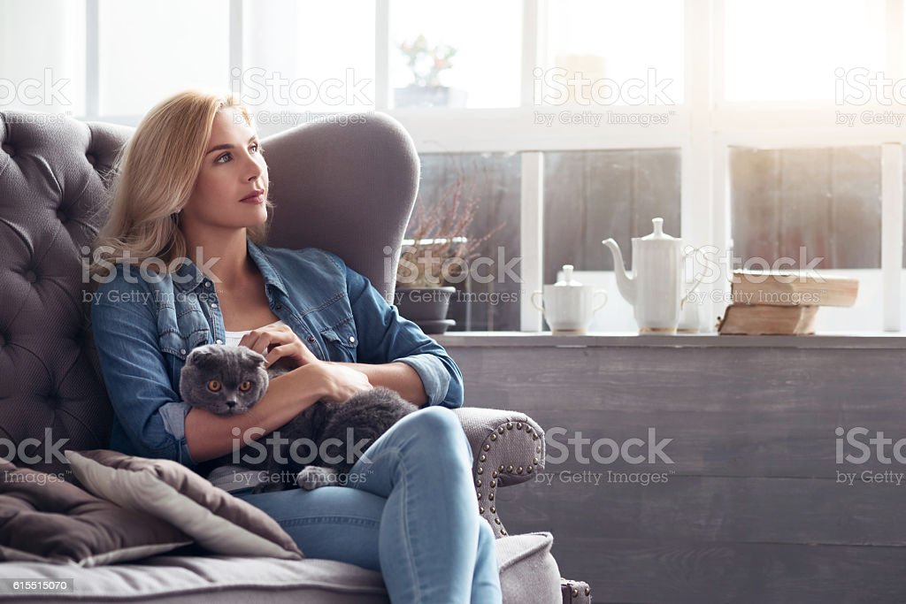 Blond woman sitting with cat on couch. - foto de stock