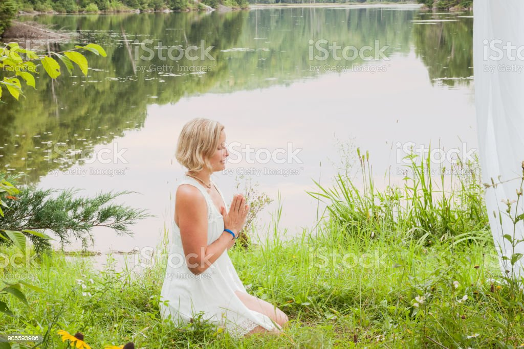 Blond woman smiling in meditation with hands over heart by a lake stock photo