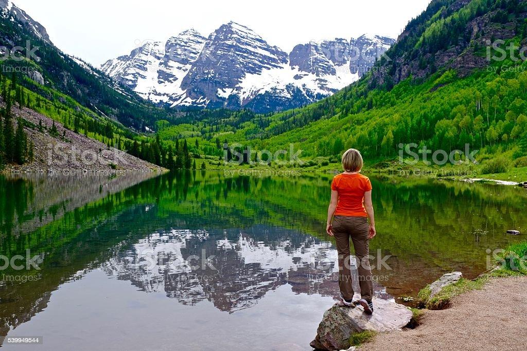 Blonde Frau stehend am See mit Blick auf die Berge und Reflexion. – Foto