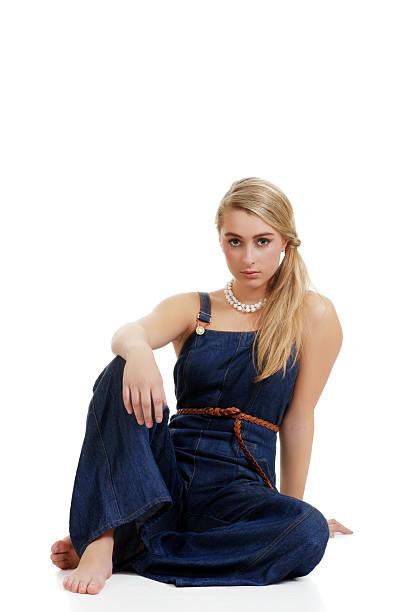 blonden frau, die jeans sitzt - jeans overall stock-fotos und bilder