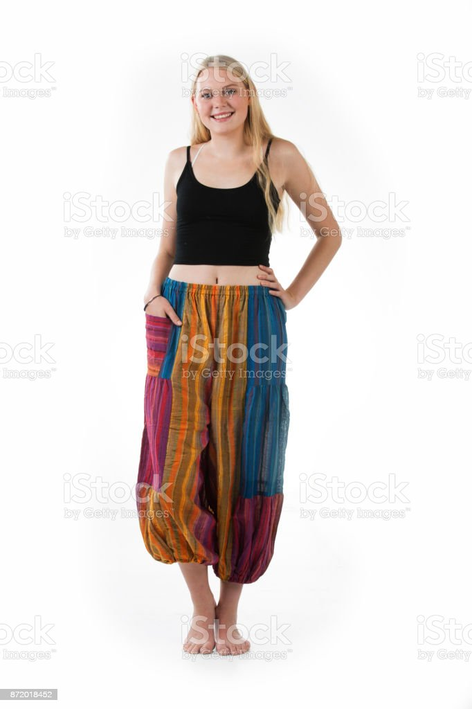 Blond woman wearing tropical rolled up rayon pants with white background stock photo