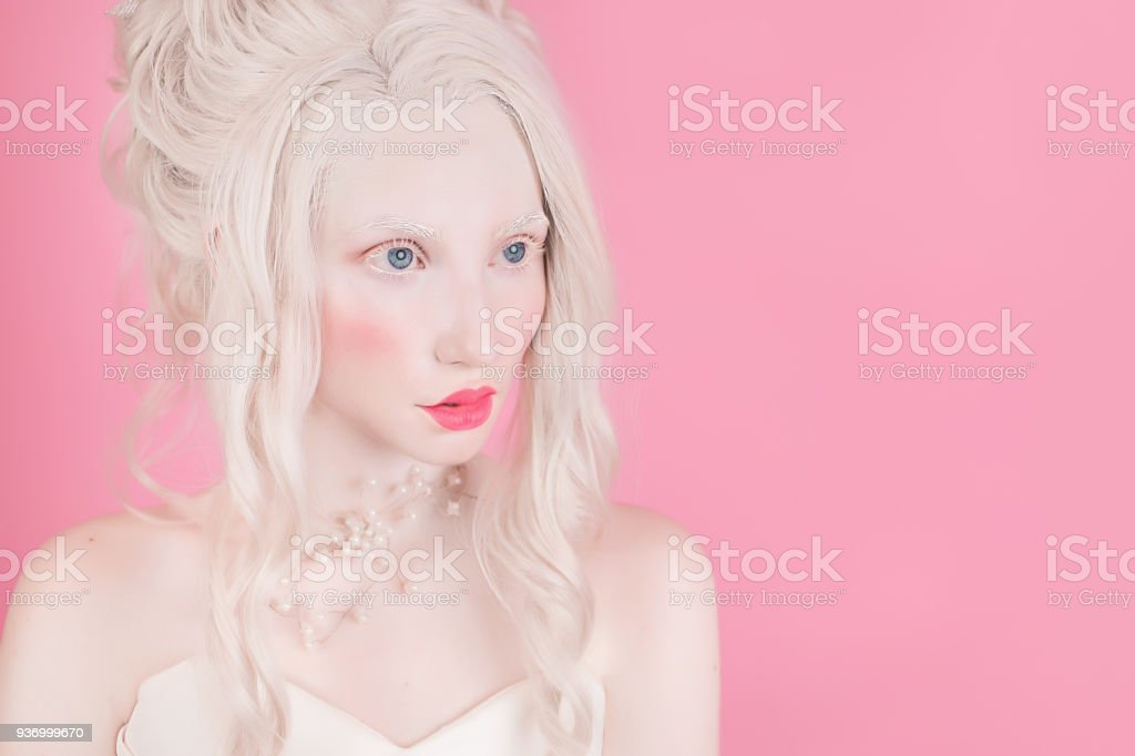 A blond woman with a beautiful luxurious rococo hair style in a white dress on a pink background. stock photo