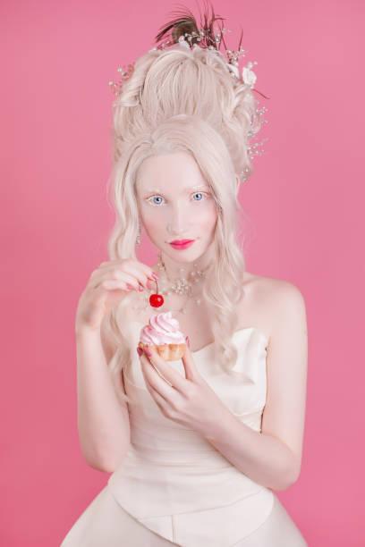 eine blonde frau mit einem schönen luxuriösen rokoko-frisur in einem weißen kleid auf einem rosa hintergrund. mädchen mit einer torte mit kirsche in der hand - festliche kleider kindermode stock-fotos und bilder