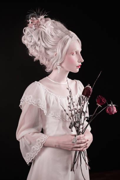 eine blonde frau mit einem schönen luxuriösen rokoko haarschnitt in einem weißen kleid mit blumen in der hand auf einem schwarzen hintergrund - festliche kleider kindermode stock-fotos und bilder