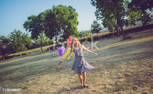 Young caucasian elegant blond woman with colorful balloons outside