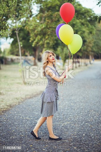 Young caucasian elegant blond woman with colorful balloons in a public park.