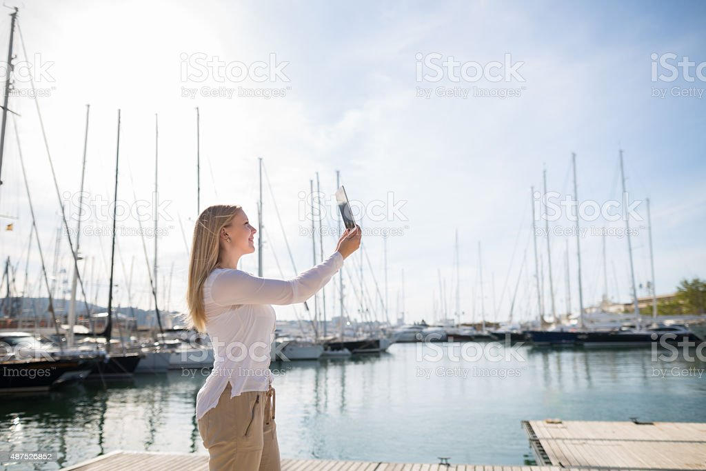 blond woman with digital tablet outdoor stock photo