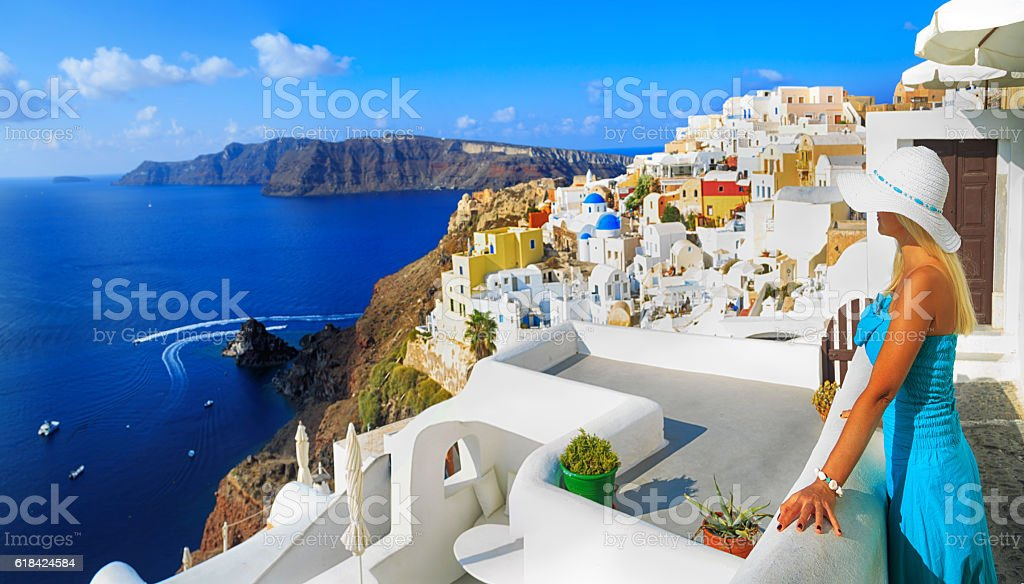 Blond woman with hat admire the beauty of Santorini stock photo