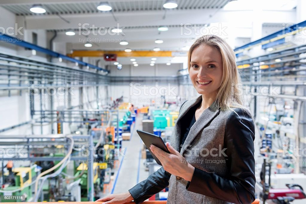 Blond woman with tablet in futuristic plant stock photo