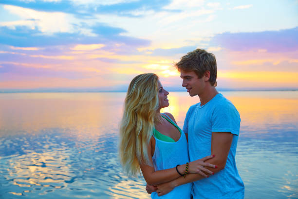 Blond young couple hug in sunset sea lake happy Blond young couple hug in sunset sea lake happy together cute teen couple stock pictures, royalty-free photos & images