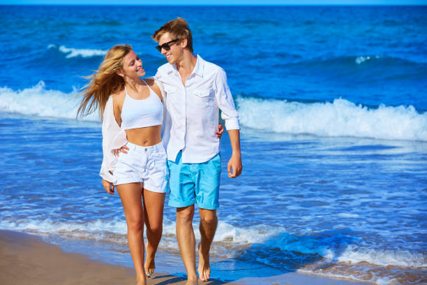 Blond young couple walking in the beach shore Blond young couple walking on the beach shore in summer vacation cute teen couple stock pictures, royalty-free photos & images