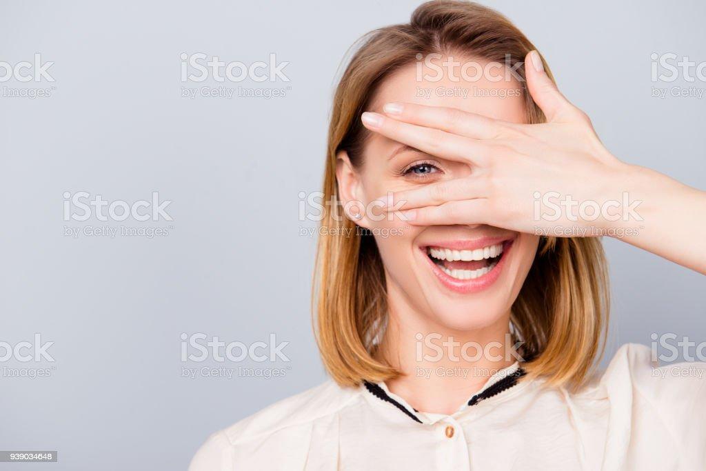 Blonde junge Frau mit strahlenden Lächeln ist durch ihre Hand suchen. Sie trägt casual-Outfit und steht auf grauem Hintergrund – Foto
