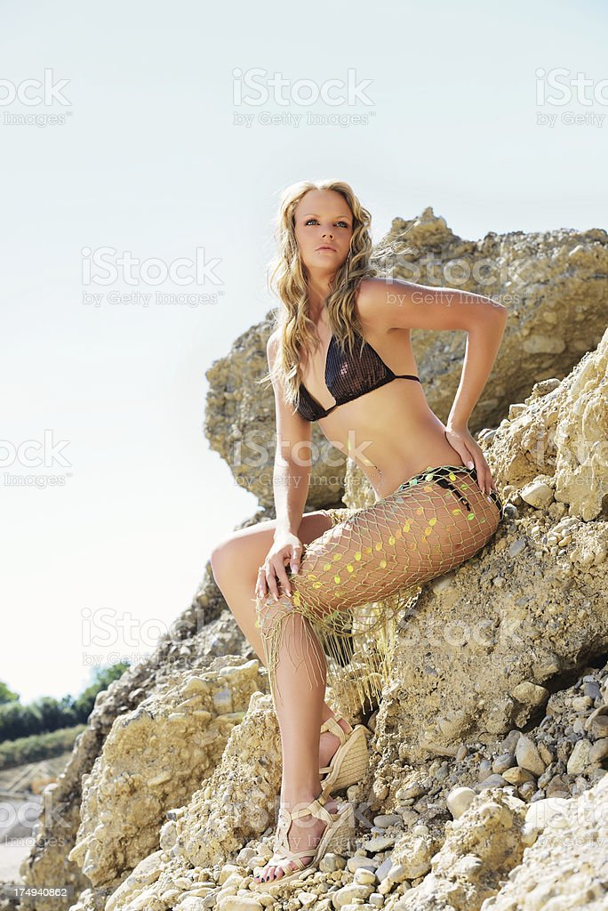 Blond Young Woman with Bikini and Net Skirt between Rocks royalty-free stock photo