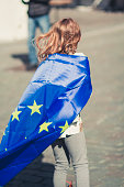 A blonde 10 year old girl sporting a european flag draped over her shoulders