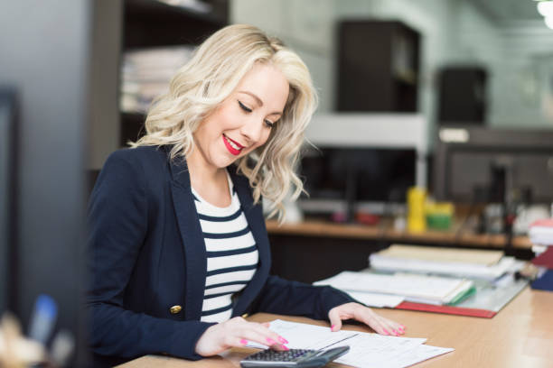 blonde 30s woman working at office and smiling blonde 30s woman working at office and smiling in office workplace sales clerk stock pictures, royalty-free photos & images