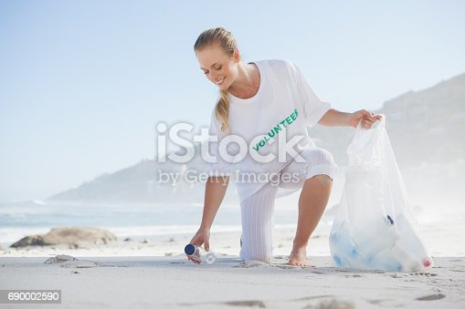 istock Blonde activist picking up trash on the beach 690002590