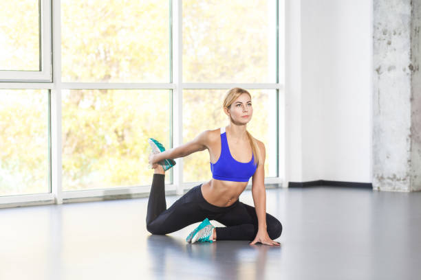 Blonde activity woman in yoga posture, king pigeon, one legged. stock photo